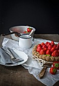 Strawberry tart with ribbon on wooden table with dishes