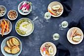 Manchego-Pesto mit Anaheim-Chili dazu Crostini, Karottensticks, Mandeln und Nüsse