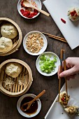 Woman s hand with chopsticks placing stuffed dumpling on sandwich paper over wooden tabletop