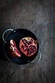 Pomegranate cut in halves in black bowl on wooden tabletop