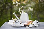 Kaffeetasse, Bücher, Hefezopf und Giesskanne mit Blütenzweig auf grauem Tischtuch