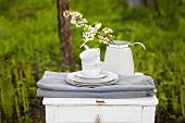 Weisser Tisch mit gefalteten Tischdecken, Geschirrstapel und blühenden Zweigen in einer Gießkanne