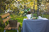 Bench, set garden table with grey tablecloth in front of flowering trees