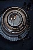 Kuchenform, Metallteller, Zinnteller und Silberlöffel auf schwarzem Untergrund