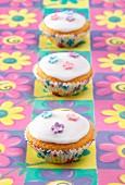 Drei Fairy Cakes mit Zuckerglasur und Zuckerblüten