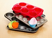 A selection of different types of baking trays and cases for making cupcakes shown on a wooden surface