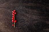 Rote Johannisbeeren auf Rispe auf rostigem Metalluntergrund