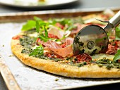 Pizza with parma ham, rocket and pesto
