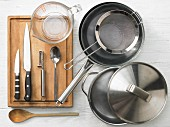 Various kitchen utensils: pot, pan, sieve, measuring cup, knife, vegetable peeler