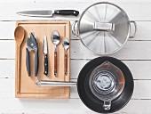 Various kitchen utensils: pot, pan, measuring cup, spoon, knife, can opener