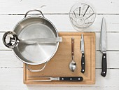 Various kitchen utensils: pot, ladle, measuring cup, meat fork, knife