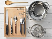 Various kitchen utensils: pots, sieves, measuring cups, can openers, knives