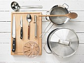 Various kitchen utensils: pot, strainer, soup ladle, measuring cup, knives