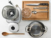 Various kitchen utensils: blender, pots, a measuring cup, spoon, knife
