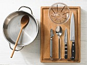 Various kitchen utensils: pot, wooden spoon, measuring cup, peeler, knives