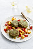 Spinach and broccoli patties on red and yellow pepper salad with mango