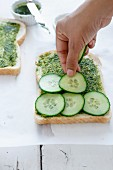 Placing Cucumber slices over spread coriander chutney on the bread