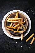 Ceramic plate of french fries with sea salt over black background