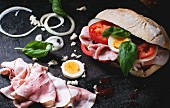 Sandwich with ham, eggs, vegetables and ketchup, served with french fries over black background