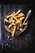 Ceramic plate of french fries with sea salt and ketchup, served with vintage fork, over black background