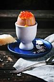 Weich gekochtes Frühstücksei mit rotem Kaviar in Eierbecher