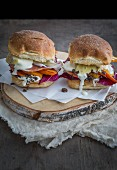 Truffle and pumpkin burgers on sandwich paper and rustic wooden board