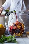 Sangria zubereiten: Wein wird in Glaskrug mit Früchten gegossen