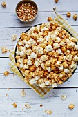 Big bowl of popcorn on white rustic background with corn seeds