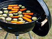 Karotten und Zucchinischeiben auf Grillrost