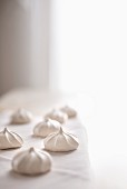 Vanilla meringue cookies on white linen with bright light background