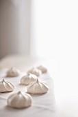 Vanilla meringue cookies on white linen with bright light background