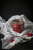 Jar of raw raspberry and chia jam in white paper before dark background