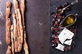 Ganze und geschnittene schwarze Oliven, Feta, Olivenöl und selbstgemachte Grissini