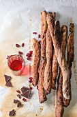 Fresh baked homemade sweet chocolate grissini bread sticks over baking paper with glass of red berry liqueur