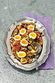 Brown lentil, potatoes and sausage salad with bacon and eggs