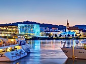 The illuminated Ars Electronica (Museum of the Future) and the River Danube in Linz, Austria