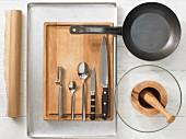 Verschiedene Küchenutensilien: Pfanne, Mörser, Sparschäler, Messer, Löffel, Backpapier