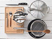 Various kitchen utensils: pots, steamer, knives, spoon, peeler