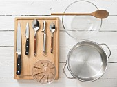 Various kitchen utensils: pot, bowl, measuring cup, knives, spoons, peeler