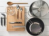 Verschiedene Küchenutensilien: Topf, Pfanne, Sieb, Messbecher, Dosenöffner