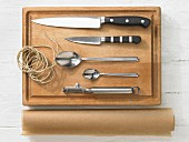 Various kitchen utensils: knives, spoons, peeler, brown string, baking paper