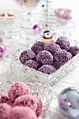 Schokoladenpralinen mit lila Zuckerperlen zu Weihnachten