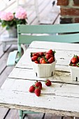 Strawberries in a cardboard bowl on a terrace table