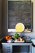 Chalkboard on wall above fruit and vegetables on old workbench in kitchen