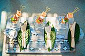 Tablett mit Holzbesteck auf Blättern und sommerlichen Spießen im Glas