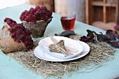 Heu-Tischset mit weißem Gedeck, Holzbesteck, Heu-Dekoherz und herbstlichem Pflanzenarrangemnt