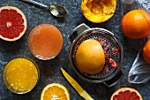 Manual metal citrus fruit extractor next to glasses of orange juice and red grapefruit juice and whole and half cut oranges and red grapefruit