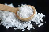 Close up of a heap of coarse salt with a wooden spoon, on black.