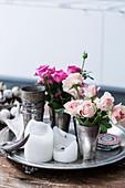 Zinnbecher mit Rosen und Kerzen auf Tablett