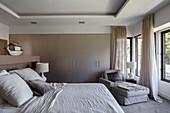 Schlafzimmer in Grautönen mit Einbauschränken und Recamiere